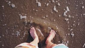 Os pés desencapados afundam-se e squish na areia marrom molhada na borda de ondas de vinda filme