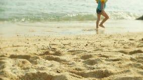 Os pés desencapados de um rapaz pequeno que esteja descansando em um Sandy Beach tropical 4k, video estoque