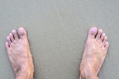 Os pés desencapados do homem na praia Textura da areia Imagem de Stock Royalty Free