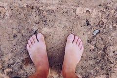 Os pés desencapados dos homens no assoalho concreto fotos de stock