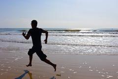 Os pés desencapados equipam o corredor na praia com ondas e reflexão Imagens de Stock