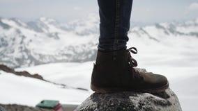 Os pés do aventureiro na bota de couro stomps na pedra na opinião cênico da montanha nevado filme