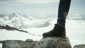 Os pés do aventureiro na bota de couro stomps na rocha na opinião cênico da montanha nevado filme
