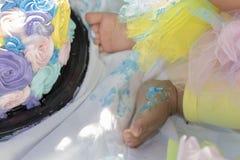 Os pés do bebê despedaçam o bolo Imagem de Stock