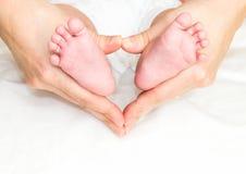 Os pés do bebê na mão da mãe Fotografia de Stock