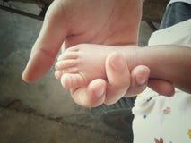 os pés do bebê nas mãos da mãe fecham-se acima com tom macio do foco e do vintage Imagens de Stock Royalty Free