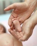 Os pés do bebê pequeno nas mãos fotos de stock royalty free