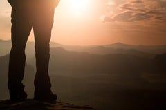 Os pés do caminhante da mulher em botas do turista estão no pico rochoso da montanha Dia ensolarado fotos de stock