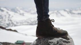 Os pés do caminhante na sapata de couro stomps na pedra na opinião cênico da montanha nevado vídeos de arquivo