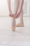 Os pés do close up da bailarina põem sobre sapatas de bailado do pointe Fotos de Stock