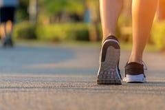 Os pés do corredor que correm na estrada no exercício exterior estacionam, close up na sapata A mulher asiática da aptidão que co fotos de stock royalty free