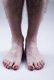Os pés do homem com verniz para as unhas vermelho Imagens de Stock Royalty Free