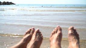 Os pés do homem e da mulher contra o mar no verão encalham, cronometram para viajar Lugar vazio para um texto filme