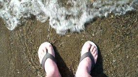 Os pés do homem lavados por ondas de oceano e enterram-nas na areia Vista superior video estoque