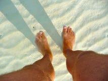 Os pés do homem na água pouco profunda Imagens de Stock Royalty Free