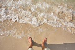 Os pés do homem na areia encalham e o mar acena Fotos de Stock Royalty Free