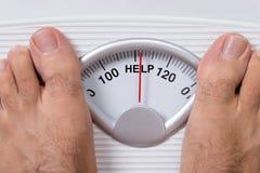 Os pés do homem na escala do peso que indica a ajuda Foto de Stock
