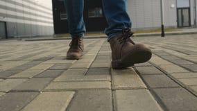 Os pés do homem nas sapatas andam no close up do pavimento vídeos de arquivo