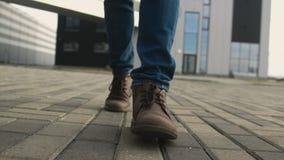 Os pés do homem nas sapatas fecham-se acima do passeio para a frente na maneira filme