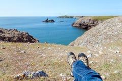 Os pés do homem que relaxam na costa rochosa de Gales do sul Imagem de Stock