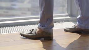 Os pés do homem que vestem calças azuis à moda e sapatas marrons do verão andam no assoalho filme