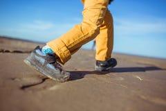 Os pés do menino que corre ao longo da praia Imagem de Stock