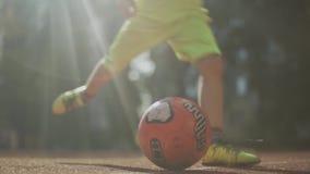 Os pés do menino retrocedem a bola O adolescente joga o futebol fora filme