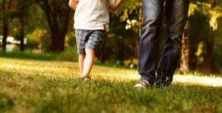 Os pés do pai e do filho andam no parque Foto de Stock Royalty Free