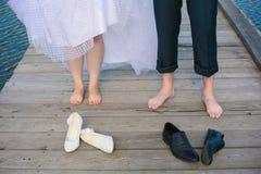 Os pés do par do casamento que estão no de madeira Fotos de Stock