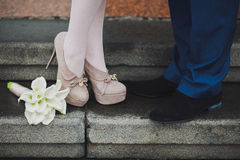 Os pés do par novo Mulher e homem no amor Primeira data datar proposta Beijo dos amantes Flores bonitas do lírio de calla Fotos de Stock