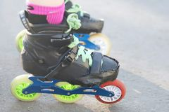 Os pés do rolo que vestem rolos para a patinagem inline e do slalom imagens de stock royalty free