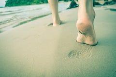 Os pés do ` s da mulher estão correndo para baixo ao mar Imagens de Stock