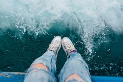 Os pés do ` s da mulher na prata rir debochadamente na frente da textura do mar fotos de stock
