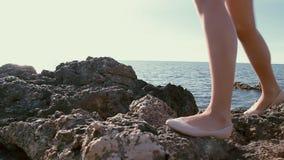 Os pés do ` s da mulher nas rochas no oceano encalham video estoque