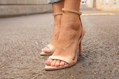 Os pés do ` s da mulher que vestem o nude aberto do dedo do pé colocam saltos Foto de Stock