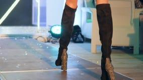 Os pés do ` s das mulheres em botas pretas da camurça no salto brilhante alto vão ao longo do pódio no desfile de moda video estoque