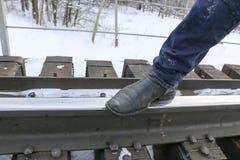 Os pés do ` s dos homens nas calças de brim e nas botas são a estrada de ferro Caminhada nos trilhos Conceito: solidão, curso, a  Fotos de Stock Royalty Free