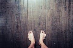 Os pés do ` s do homem estão na madeira velha da prancha Fotos de Stock