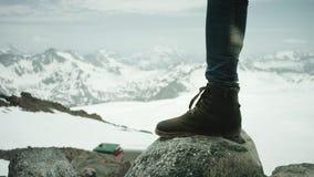 Os pés do viajante na bota de couro stomps na rocha na opinião cênico da montanha nevado video estoque
