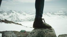Os pés do viajante na sapata de couro stomps na rocha na opinião cênico da montanha nevado vídeos de arquivo