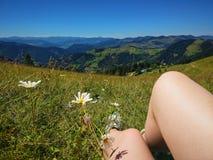Os pés do viajante que sentam-se em uma montanha alta cobrem no curso Fotografia de Stock