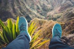Os pés do viajante que streching abaixo de seus pés sobre a montanha excitante ajardinam com picos de montanha, penhascos ásperos Fotos de Stock
