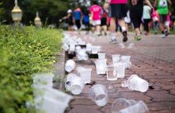 Os pés dos corredores de maratona e os copos emptry da água no rafrescamento apontam Imagem de Stock Royalty Free