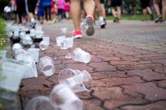 Os pés dos corredores de maratona e os copos emptry da água no rafrescamento apontam Fotografia de Stock Royalty Free
