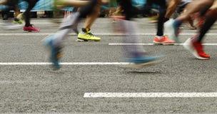 Os pés dos corredores na estrada no borrão fazem sinal foto de stock royalty free