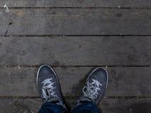 Os pés dos homens nas sapatilhas estão no assoalho de madeira As sapatilhas elegantes dos homens foto de stock royalty free