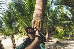 Os pés dos homens no short que encontra-se em uma rede imagem de stock royalty free