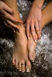 Os pés e as mãos da jovem mulher fecham-se acima acima da vista, menina que toca em seus pés no fundo abstrato artístico preto e  imagem de stock royalty free