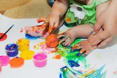 Os pés e as mãos das crianças na pintura Foto de Stock