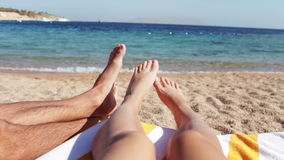 Os pés encontram-se em um vadio do sol na praia vídeos de arquivo